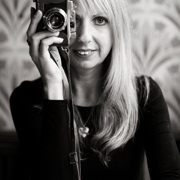 Portrait of Hayley sat holding vintage camera up to right eye - photographer at Raw Photography